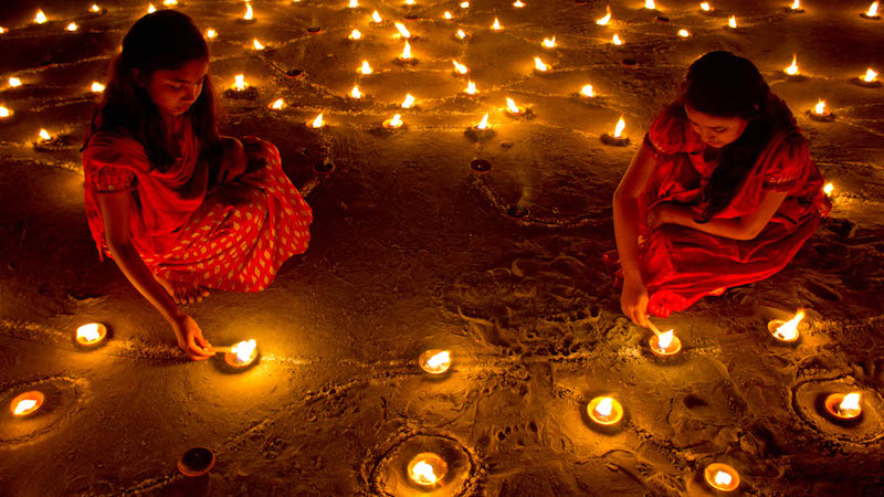 photo of girls lighting candles at Diwali: Lights of India event